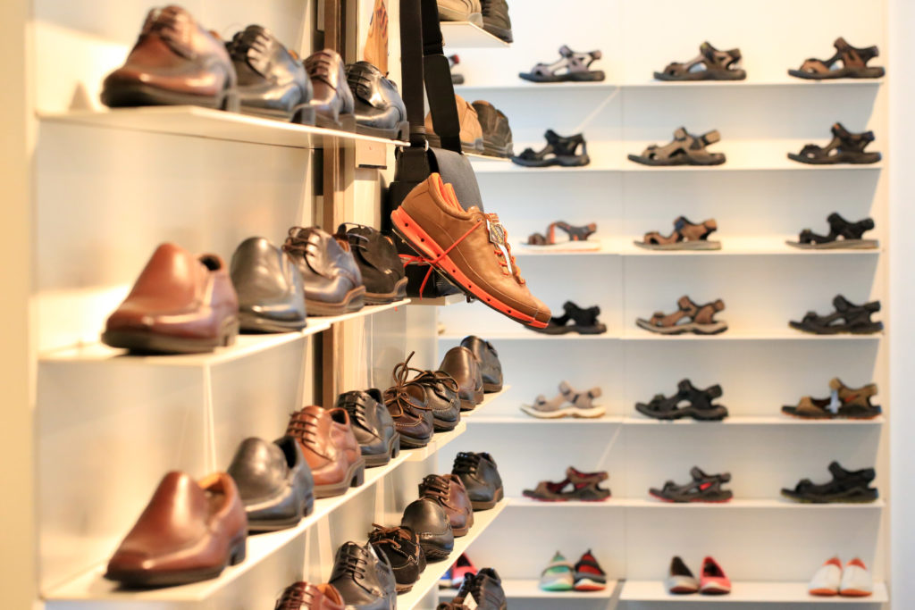 Leather shoes, sneakers and sandals on shelves.