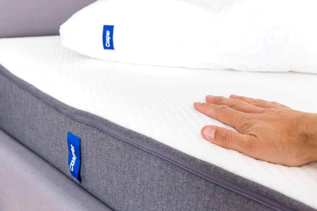 Hand placed on white mattress