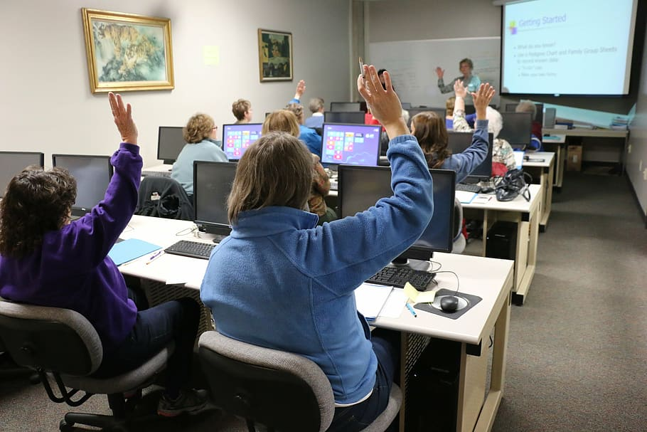 person raising hand, classroom, computer, technology, training, classmates, computer, class, learning, pc, people, education, indoors, seminar, student, business, real, people, men, group of people, sitting, women, males, boys, table, school, adult
